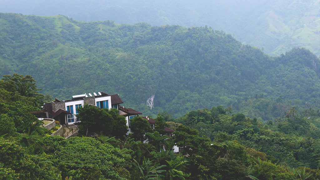 The available villas at West 35 Eco Mountain Resort overlooking the lush green mountains .